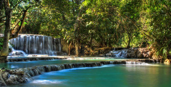 Bestaunen Sie die Kuangsi Wasserfälle, die die Becken Türkis färben.