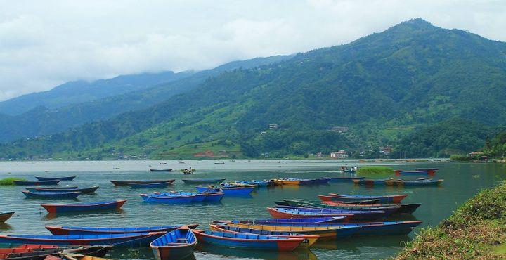 Sie unternehmen eine Bootsfahrt auf den Phewa-See und genießen eine herrliche Aussicht auf die umliegenden Berge.